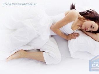 Fata care doarme intr-un pat cu asternut alb
