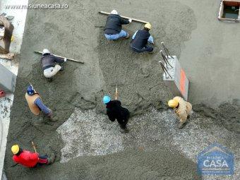 Muncitori care toarna si niveleaza beton