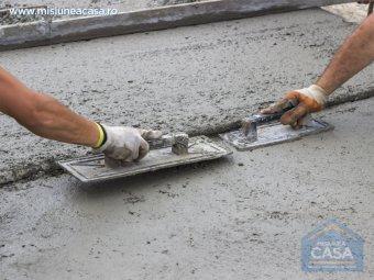 Meseriasi care intind betonul cu gletiera