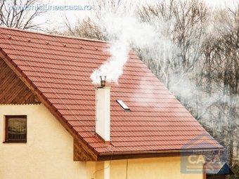 Acoperisul unei case cu cos de fum pe care iese fum.